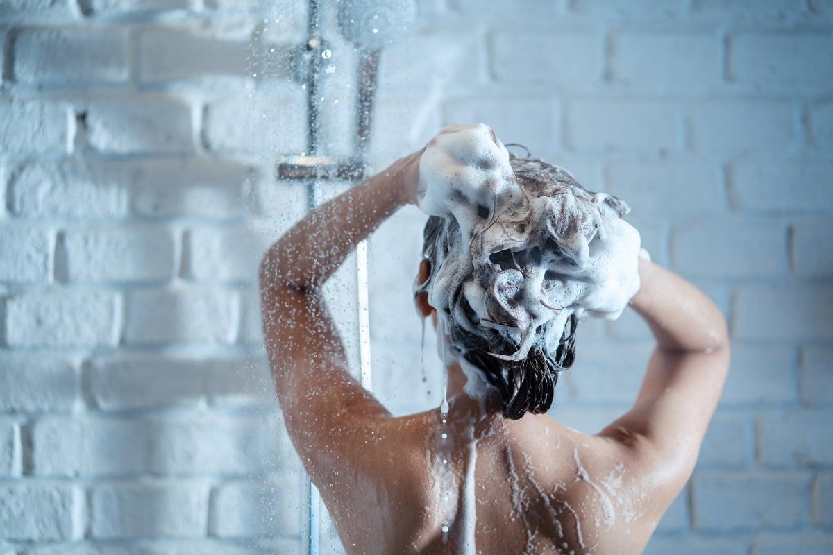 kobieta bierze prysznic i myje włosy szamponem na przetłuszające się włosy